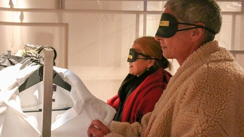 Two visitors with blindfolds feel the exhibits.