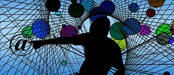Person in a net is surrounded by colourful balls, points to an @