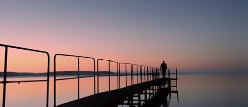 a person stands on a jetty and looks into the distance