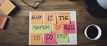 "Der auf den Stickern geschriebene Satz: ""What is the Minimum of Rules to co exist""."