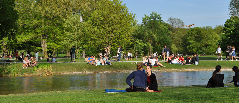 Groups of people sit by a stream in the English Garden.