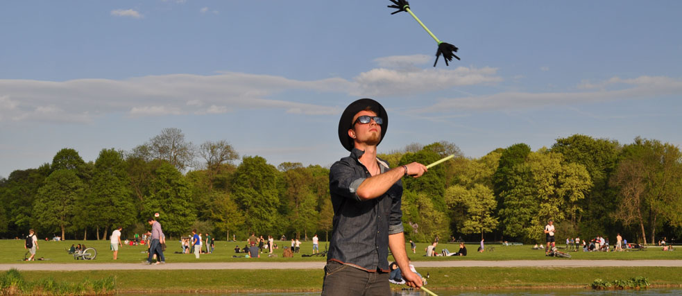 A young man juggling flowersticks in a park.