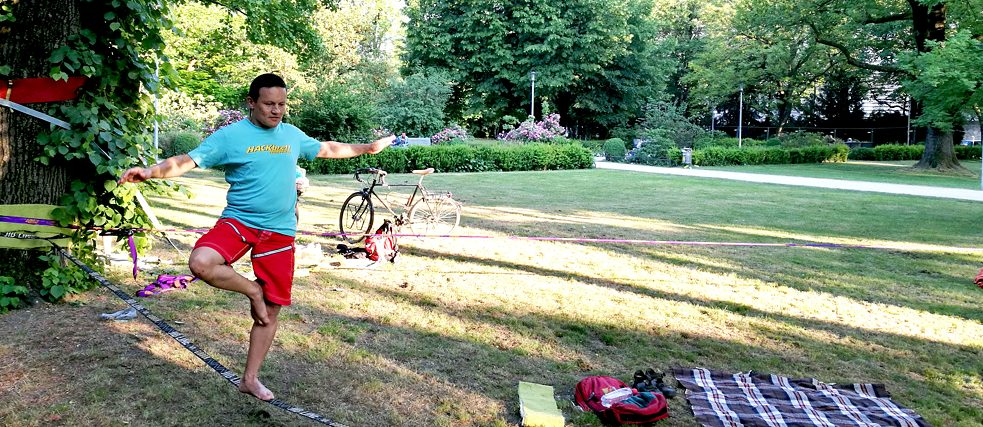 A man balancing on a slackline in a park.