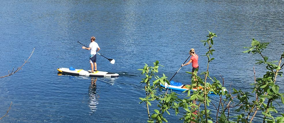 A man and a woman are doing stand-up paddling.