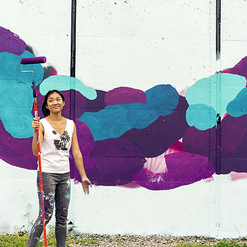 Wing Chow works on her mural for POW! WOW! DC 2018