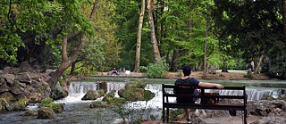 A man sits on a bench and looks at a waterfall.