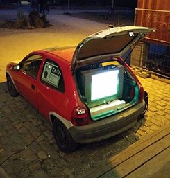A TV set up in the boot of a car.
