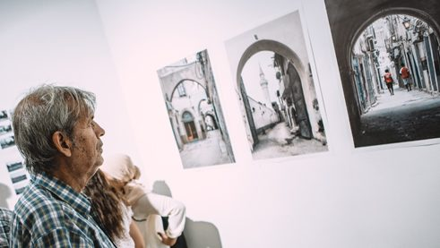 "A visitor of the exhibition ""Portion of Libya"" looking at pictures of Heba Alshibani"