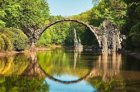 <b>Rakotzbrücke: Devil's bridge with the perfect reflection</b><br/>Anyone keen on photo safaris should definitely head for the Rakotzbrücke at Kromlau in Saxony. Built in 1882 in a landscaped park that is Germany's largest rhododendron garden, the &#x22;devil's bridge&#x22; forms a perfect circle with its reflection in the waters of the lake below. The extraordinary sight is made all the more magical by the basalt rocks thrusting out of the water.