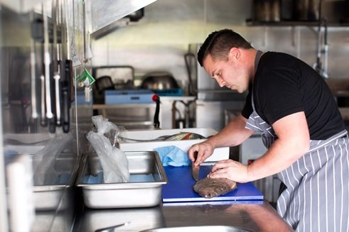 Chef Logan Coath filleting John Dory in the Archive kitchen