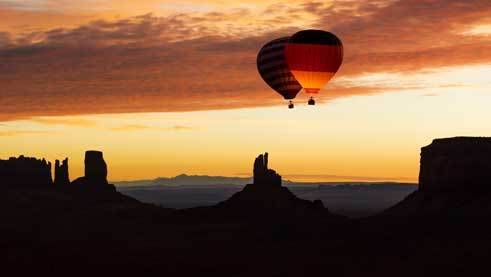 Despite rough winds over Monument Valley, the two hot-air balloons launch in the sunrise.