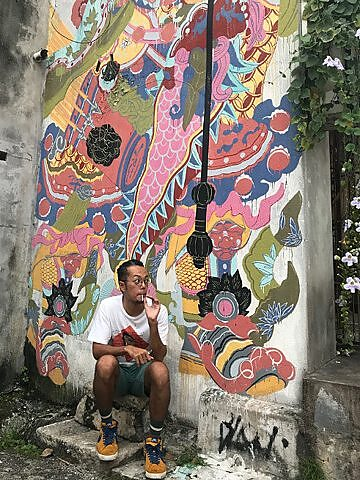 Street artist Bibichun in front of his work. It's much easier for foreign artists to get commissions in Malaysia, he says.