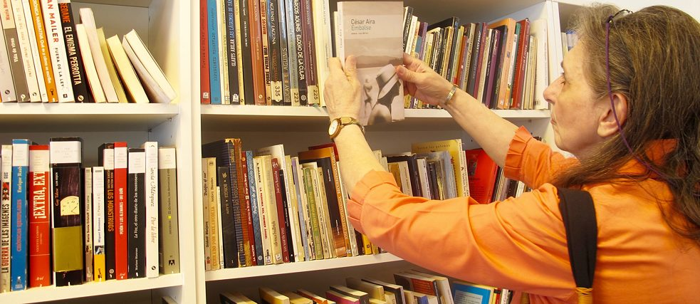 Mirta browses the contemporary literature section at the Casa de la lectura