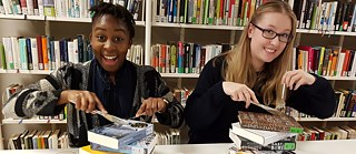 Two girls with cutlery in their hand pretend to eat a pile of books.