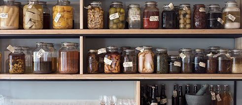 A wall of preserves and pickles line the wall in the restaurant