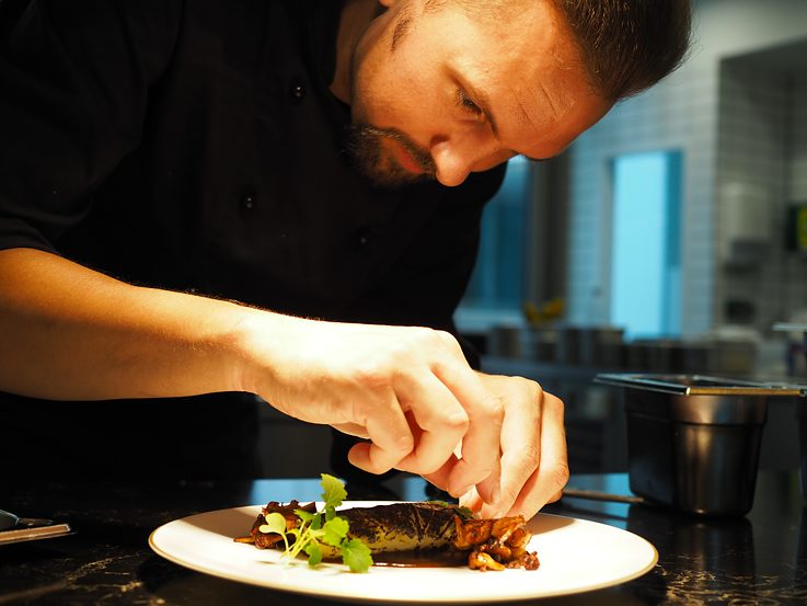 Helge Hagemann is plating a dish