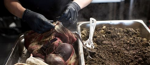 Sous chef Maxime Gnojczak uncovers the beetroot which have been baking in soil