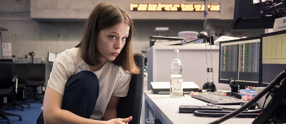 """Bad Banks - The man from London"": noticeably tired and overworked, Jana (Paula Beer) sits in the office at night and works. The young woman has taken off her shoes, squats on her office chair with her legs drawn up, and looks almost apathetically at the monitors in front of her."