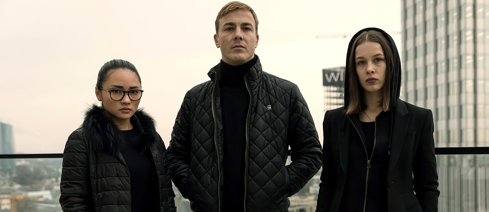 """Bad Banks - The Lion's Den"": Jana (Paula Beer), Adam (Albrecht Schuch) and Thao (Mai Duong Kieu), dressed in black, stand side by side on the roof terrace of a skyscraper overlooking Frankfurt and pose for the camera."