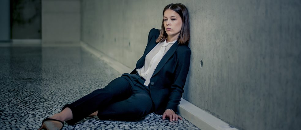"""Bad Banks"": Jana Liekam (Paula Beer) sits exhausted on the floor in a large, empty room. She leans against the barren concrete wall."