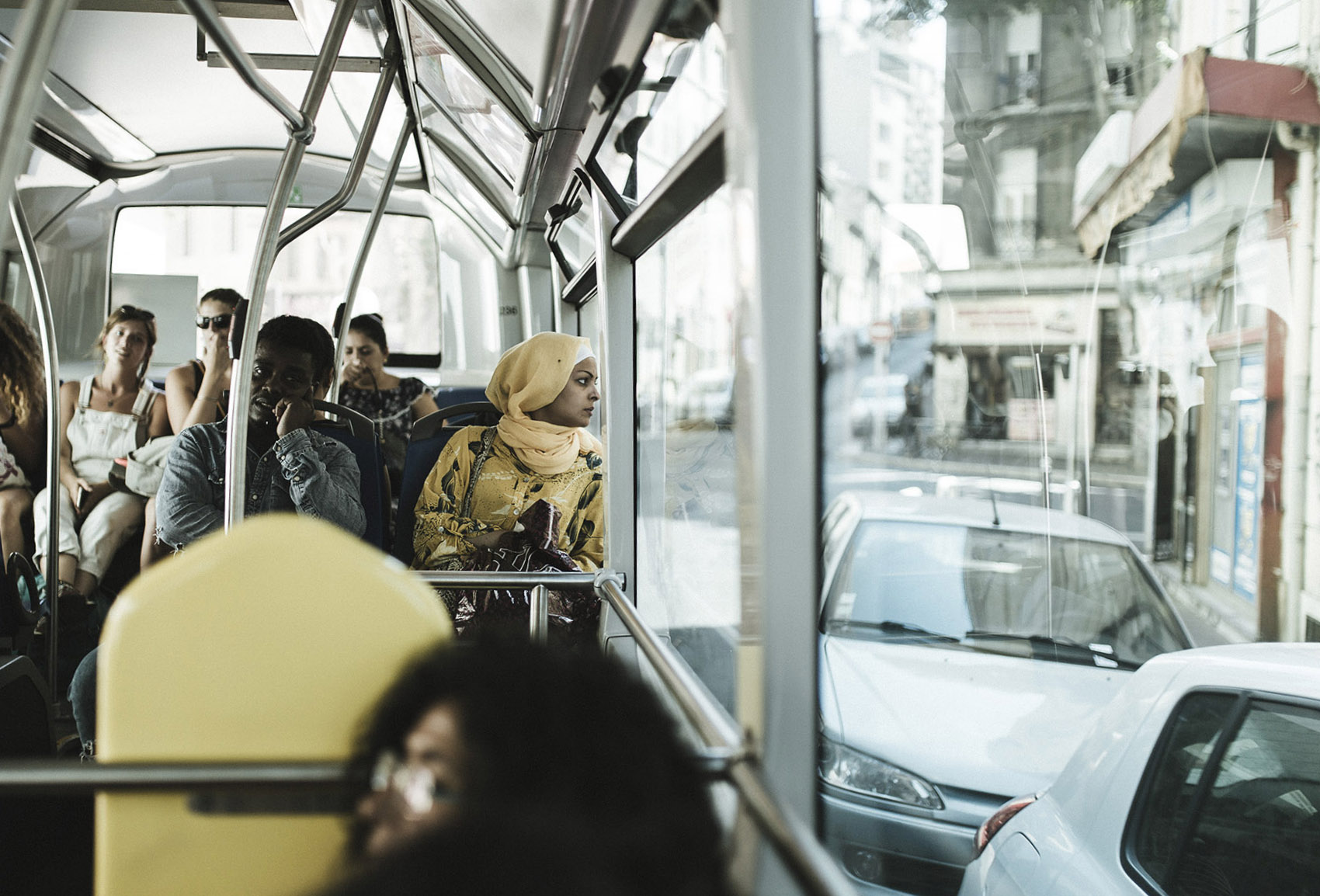 A woman watches the city from a bus window.