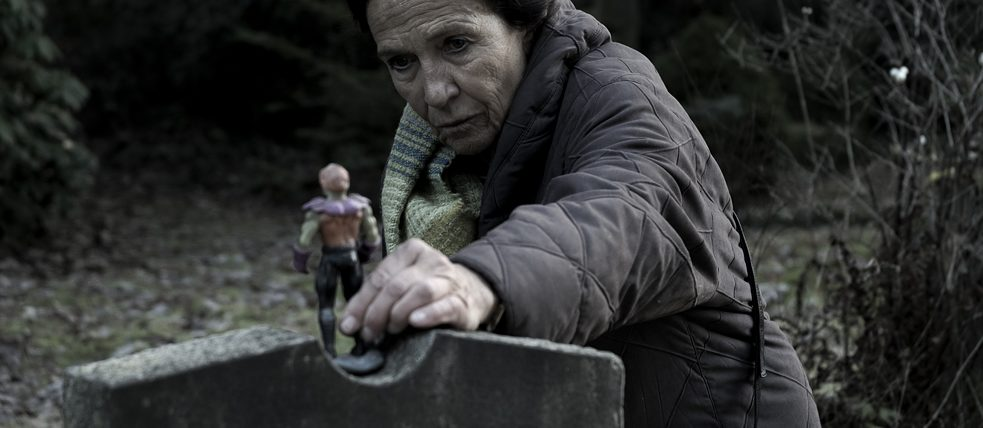 Dark production still: An old women places an action figure on a gravestone.