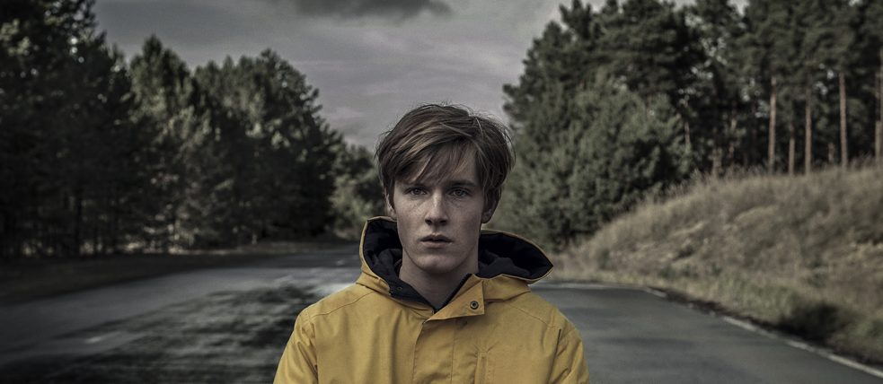 Jonas Kahnwald (played by Louis Hofmann) is standing alone in the middle of a wide street.