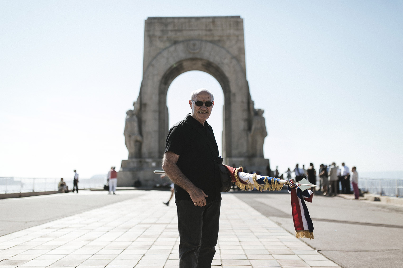 The pensioner Francis is standing in front of Porte d'Orient, holding a rolled-up flag and looking into the camera.