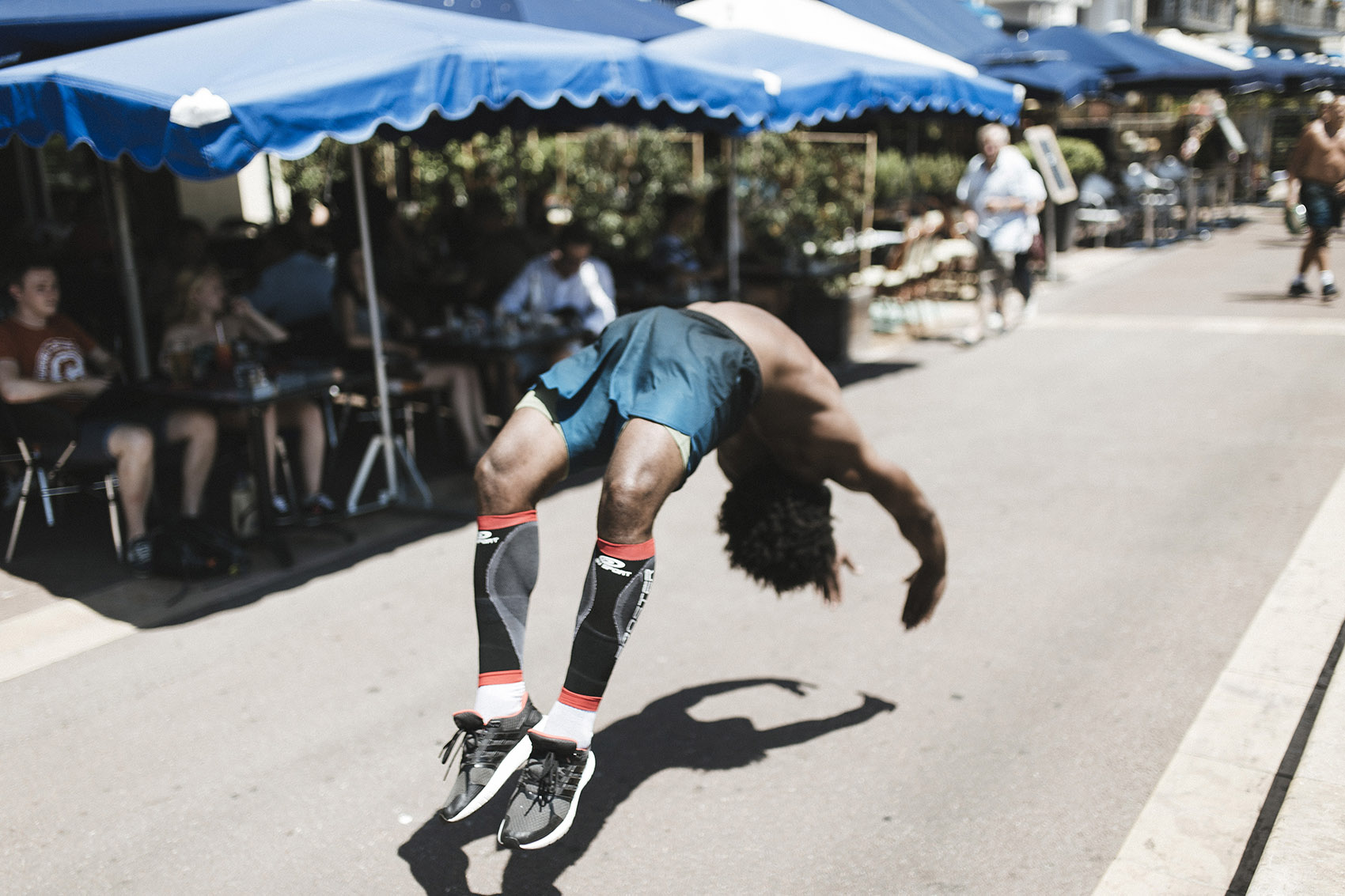 Capoeira dancers performs a backflip on the pavement.
