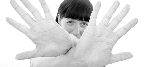 A woman cups hands in front of her face
