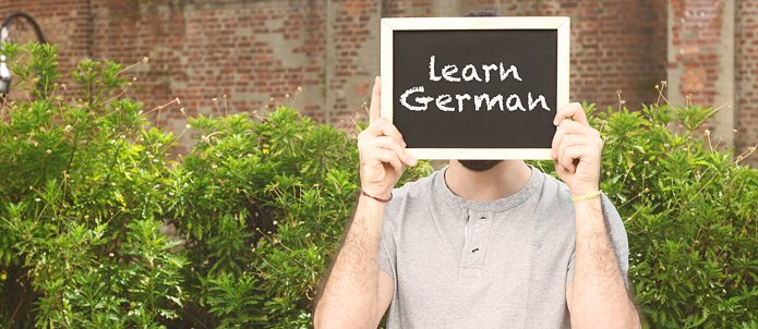 "Portrait of young man holding chalkboard with text ""Learn German"". Education concept, Stock image"