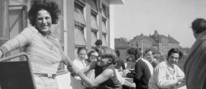Gymnastics teacher Karla Grosch, who played a key role in the performances of the drama class, jokes with students on the terrace in front of the Bauhaus canteen