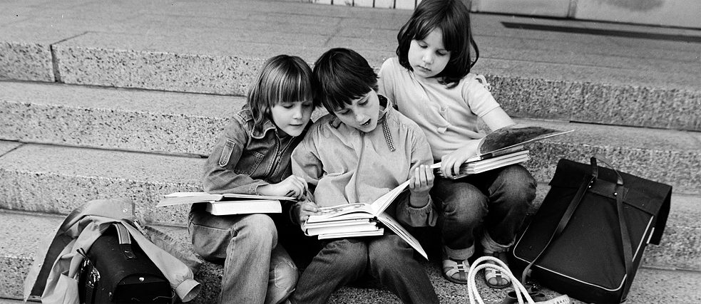 Three children sitting on a staircase looking at books.