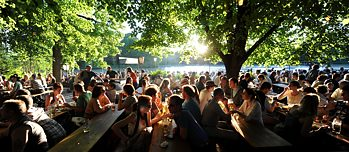 Beer garden guests sit under trees in a beer garden in Munich