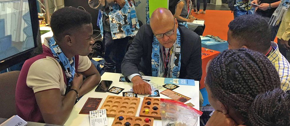 (Left to right): Moses Ayantunde (Lagos, Nigeria), Johannes Ebert, secretary-general of the Goethe-Institut, Kirubel Habtu (Addis Ababa, Ethiopia) and Adefoyeke Ajao (Lagos, Nigeria) playing the mega-game Busara launched at the Enter Africa stand of the Indie Arena Booth at gamescom
