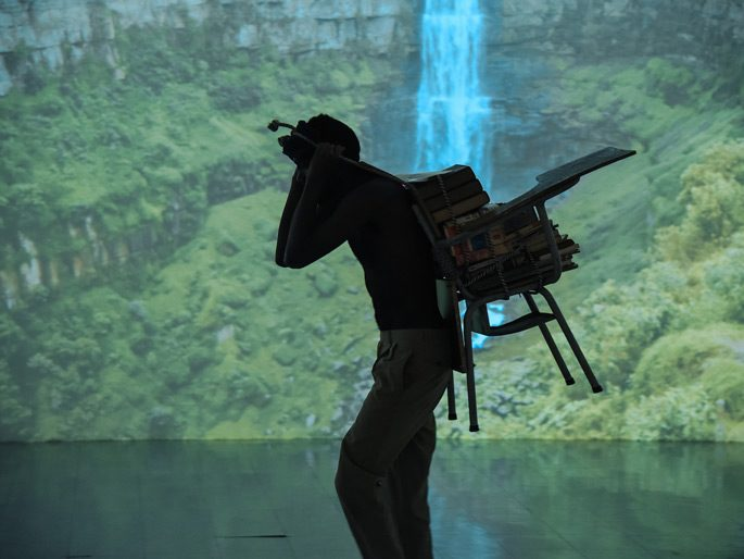 Jean Carlos Lucumi, The Freight Carrier, Performance in front of José Luis Bongore's video installation