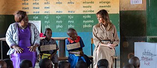 US First Lady Melania Trump, alongside Maureen Masi, Head Teacher of Chipala Primary School in Lilongwe, Malawi, observes children learning the English and Chichewa languages
