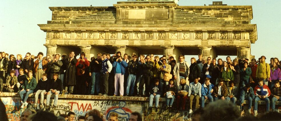 Locals celebrate on top of the opened Berlin Wall in 1989