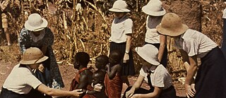 """German girls in a native village with their teacher. The Wanyakusa Woman proudly shows off her children"": German East Africa / Photo c. 1941 (formerly German colony, now Tanzania)"