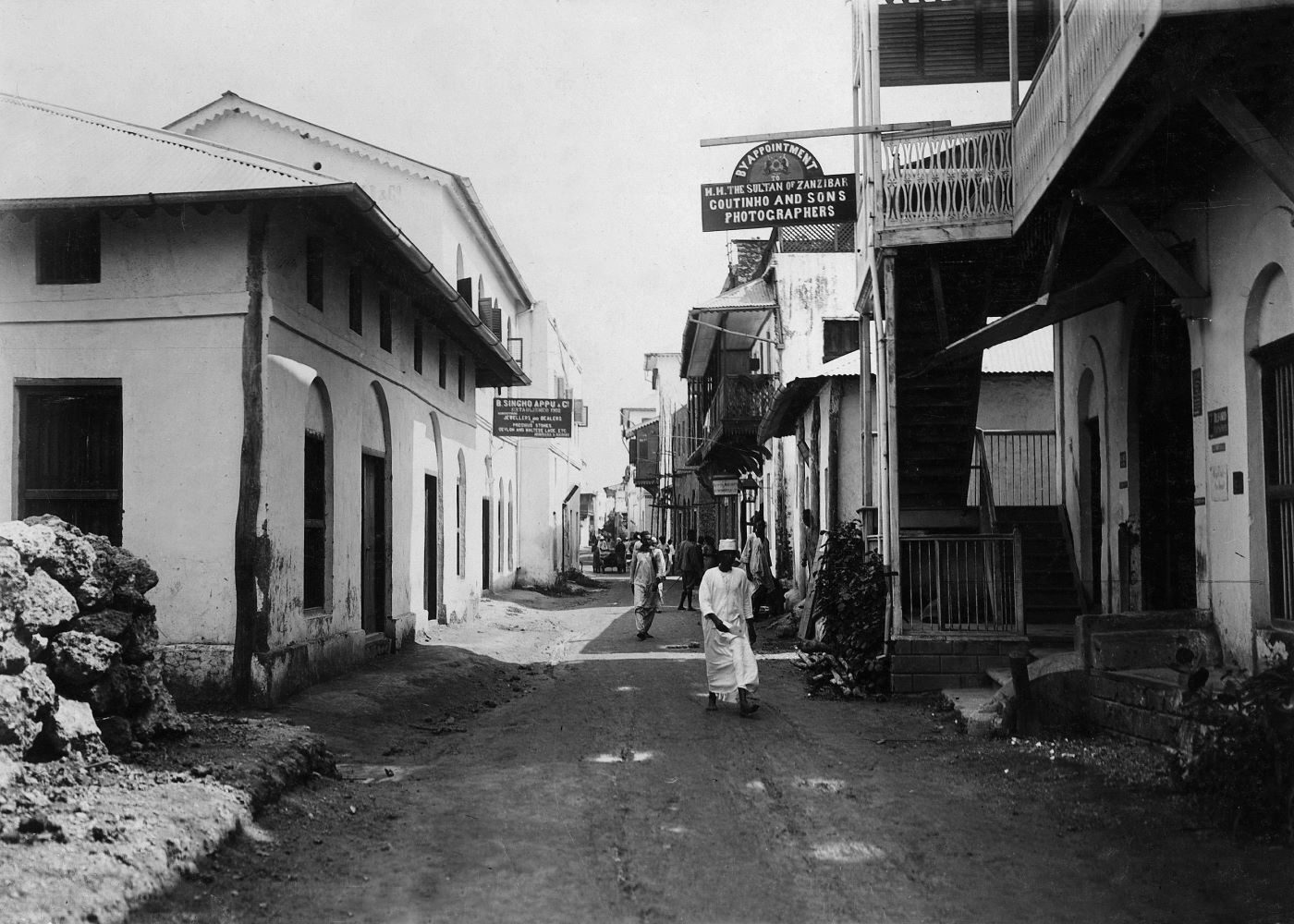 British East Africa, Kenya, Mombasa Island, Mombasa: View of a street; left: 'B. Singho Appu' (jewellers and traders, among others with gemstones), right: photographer's Studio– undated, probably around 1910s
