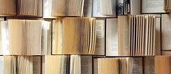 Open books are piled up to form a wall.