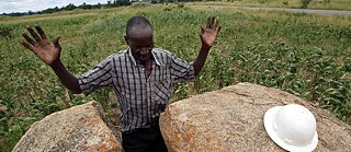 Praying for a good harvest in the barren maize field
