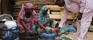 Everyday life 2017: Family cooking in Maiduguri (Nigeria) in front of their hut