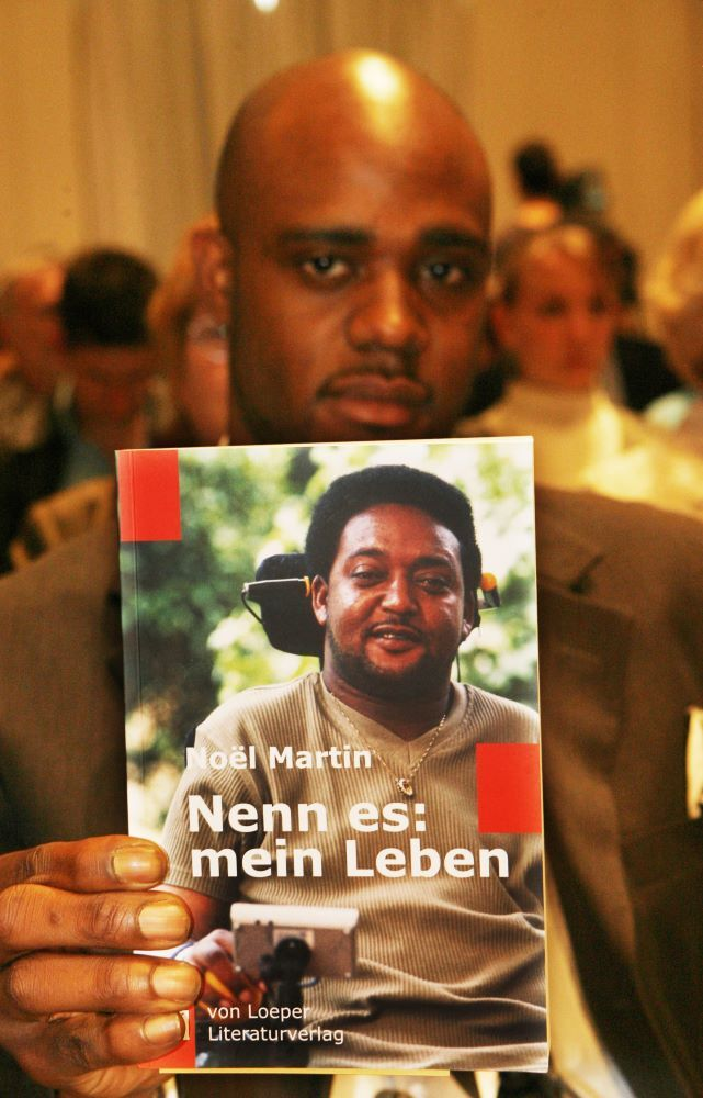 "Negus Martin with his father's book ""Nenn es: mein Leben"" (Call it: my life). The colored Briton Noel Martin was the victim of a xenophobic attack in the German community of Mahlow (Teltow-Fläming) in 1996. The 47-year-old Noel Martin, who lives in Birmingham, England, has been paraplegic ever since. Through a fund he promotes youth exchange and is active against racism."