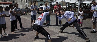 capoeira at the Ver-o-Peso riverside market in Belém, Brazil. Capoeira is an Afro-Brazilian martial art that combines elements of dance, acrobatics and music. It was developed by enslaved Africans in Brazil.