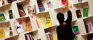 A woman sorts books on a shelf in the pavilion of the host country Brazil at the Book Fair in Frankfurt am Main 2013