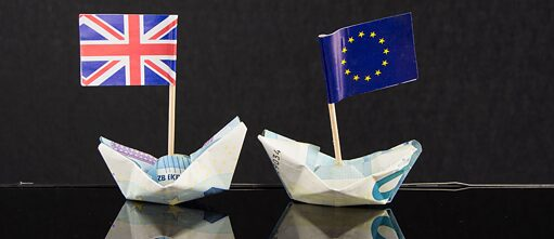 Two boats folded out of Euro banc notes; one with a flag of the EU, the other one with a UK-flag; black background