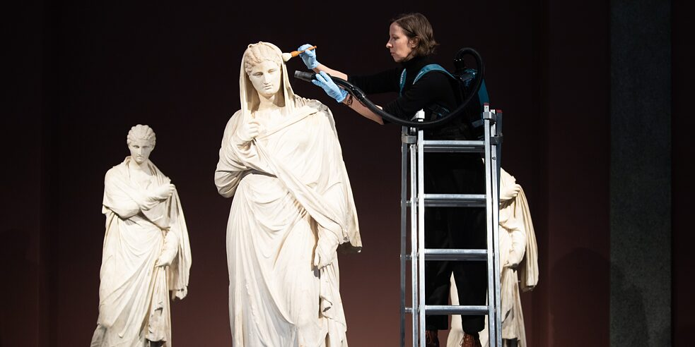 The three marble statues known as the Herculaneum Women are the highlight of the antiquities gallery, here enjoying a final cleaning from the head of the sculpture collection right before the grand reopening.