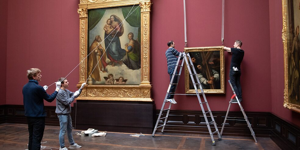 "Raphael's ""Sistine Madonna"" hangs directly one floor above. The painting ""Christ Bearing the Cross"" is being hung just to its right."