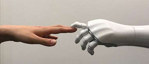 A human hand touches a robotic hand.
